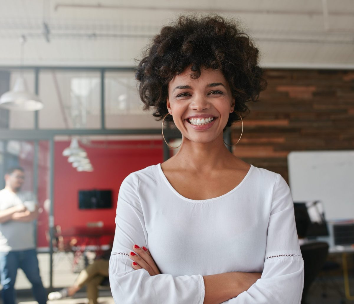 smiling-young-woman-standing-in-creative-office-PHKL7DX-scaled.jpg
